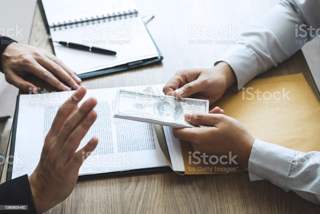Anti bribery and corruption concept, Business man refusing and don't receive money banknote offered from business people to accept agreement contract of investment deal stock photo