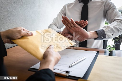 Anti bribery and corruption concept, Business man refusing and don't receive money banknote in envelop offer from business people to accept agreement contract of investment deal.