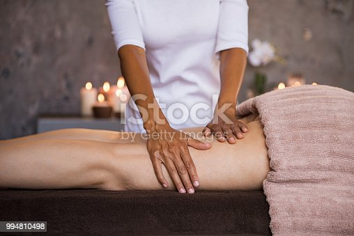 Therapeutic massage for senior woman by beautician at spa salon. Closeup of professional masseuse hands massaging woman legs at wellness center. Anti cellulite treatment and leg drainage on mature woman.