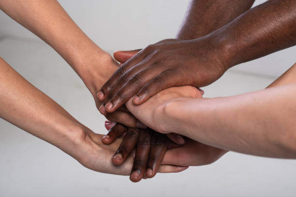 Anti racist studio shot of unrecognizable group of people holding hands stock photo