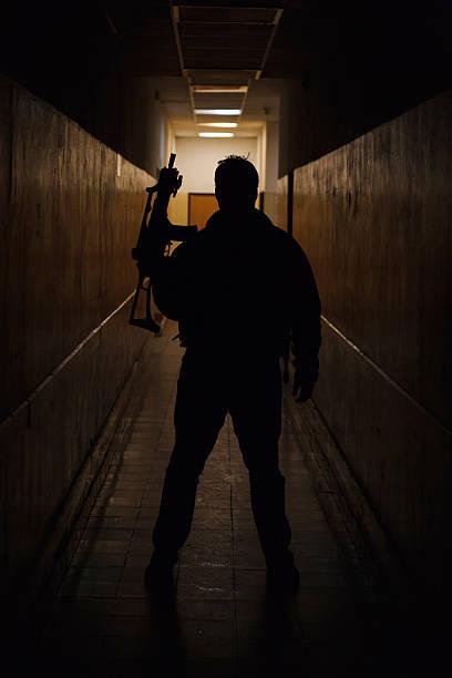 Anti terrorist dressed in camouflage, standing with gun, studio shot Anti terrorist standing with a gun in the dark corridor antiterrorist stock pictures, royalty-free photos & images
