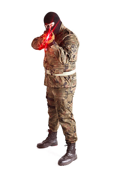 Anti terrorist pointing at camera gun with red laser sight Anti terrorist dressed in camouflage, pointing gun at camera with red laser sight, studio shot antiterrorist stock pictures, royalty-free photos & images
