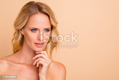 istock Anti-age novelty concept. Close-up portrait of attractive charming wavy-haired lady with flawless smooth shine fresh skin touching chin copy empty blank space place isolated on beige background 1132239934