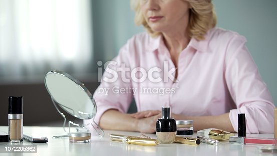 istock Anti-aging cosmetics on table with senior woman on background, beauty care 1072205362