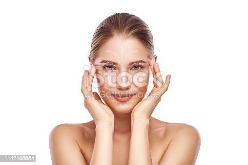istock Anti-aging facial massage. Beautiful young woman with white arrows over her face keeping hands on head and looking at camera. Isolated on white background. Skin Care. Massage lines 1142168854