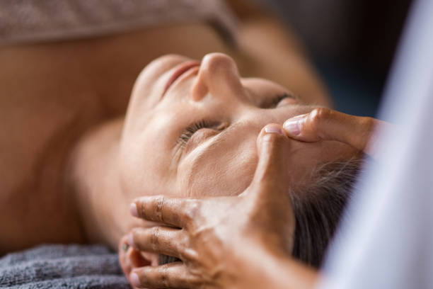Anti-aging facial treatment Closeup face of mature woman having facial massage at spa. Senior woman lying with closed eyes at spa while a massage therapist doing anti-aging treatment. Masseur doing head massage at wellness center. massaging stock pictures, royalty-free photos & images