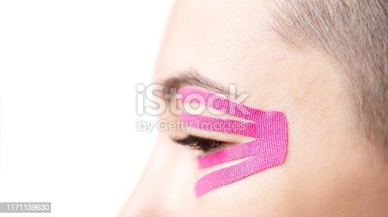 istock Anti-aging kinesiology tape on female eyelid, close-up. 1171139630