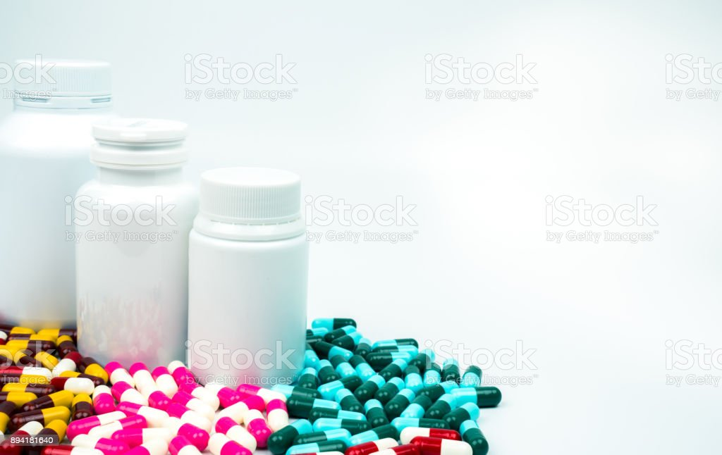 Antibiotic capsules pills and plastic bottle with blank label isolated on white background with copy space. Drug resistance concept. Antibiotics drug use with reasonable and global healthcare concept. stock photo