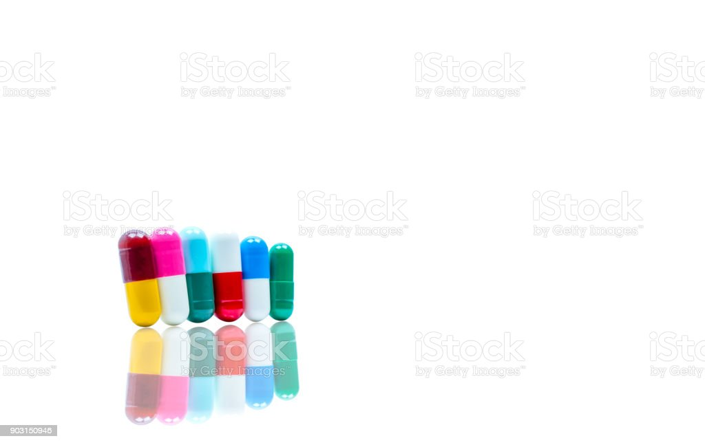 Antibiotic capsules pills in a row on white background with shadows and copy space. Drug resistance concept. Antibiotics drug use with reasonable and global healthcare concept. stock photo
