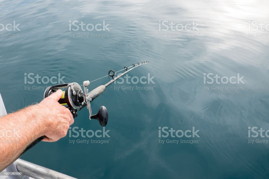 Anticipation of catching a fish: man's hand holding fishing rod pole with line in water in Far North District, Northland, New Zealand, NZ stock photo
