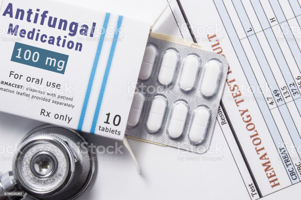 Antifungal drug. Open paper packaging box of medication with name group of drug Antifungal, blister with pills, next to stethoscope and blood test results. Concept for treatment of fungal diseases stock photo