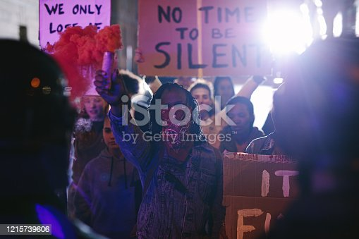 Protestors demonstrating with smoke grenades in front of the security force at night. Anti-government protest by the social activist group.