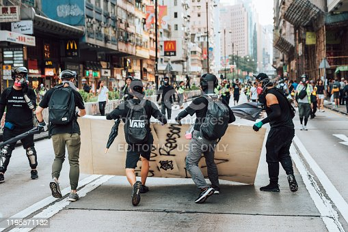 Kowloon, Hong Kong - October 20, 2019:  Protesters dressed in black and with black clad holding sticks during the demonstration. Anti-government protesters blocked roads and subway accesses in the Kowloon district of Hong Kong.
