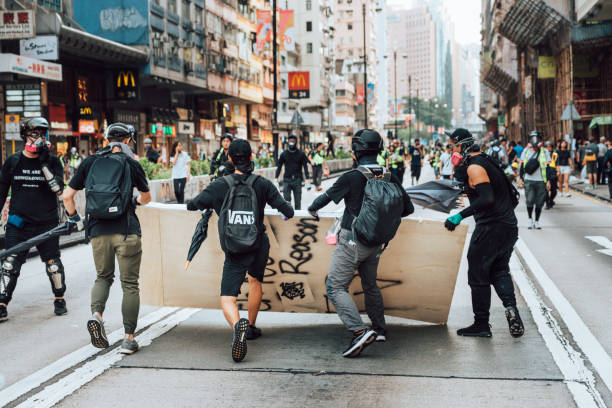 Anti-government protesters in Hongkong Kowloon, Hong Kong - October 20, 2019:  Protesters dressed in black and with black clad holding sticks during the demonstration. Anti-government protesters blocked roads and subway accesses in the Kowloon district of Hong Kong. riot stock pictures, royalty-free photos & images