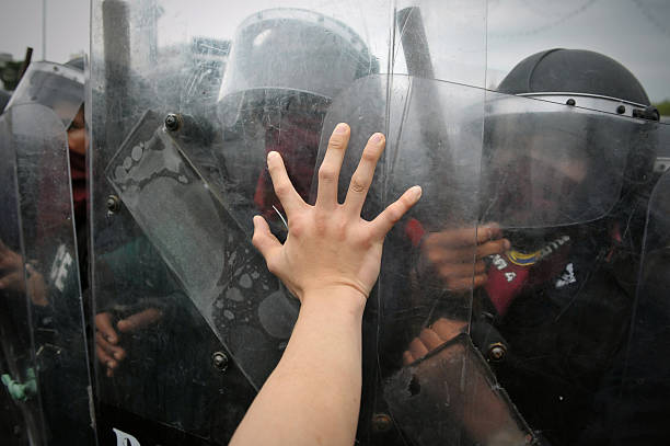 Anti-Government Rally in Bangkok Bangkok, Thailand - November 24, 2012: A protester from the nationalist Pitak Siam group pushes against a police riot shield during a large anti-government rally on Makhawan Bridge. riot police stock pictures, royalty-free photos & images