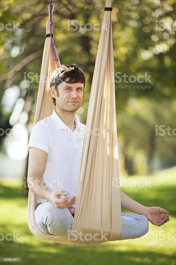 Anti-gravity Yoga, man doing exercises in the park stock photo