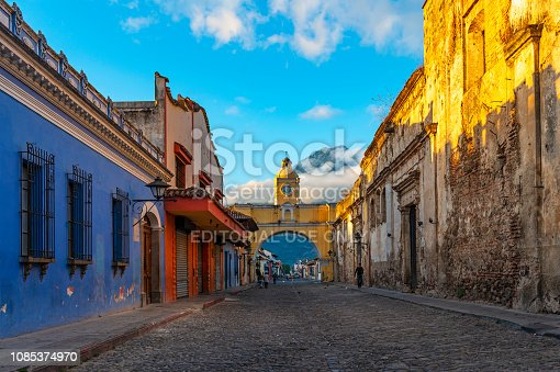 Cityscape with people walking in the Main Street of Antigua city at sunrise, with the yellow arch and Agua volcano in the background, Guatemala, Central America.