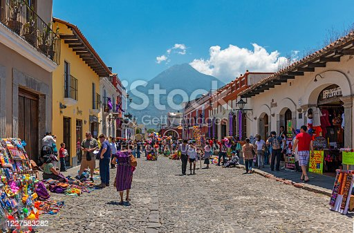 People walking in the main street of Antigua with the Agua volcano in the background.