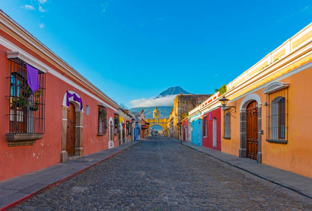Antigua Cityscape at Sunrise, Guatemala Cityscape of the colorful main street of Antigua city at sunrise with the famous yellow arch and the Agua volcano in the background, Guatemala, Central America. central america stock pictures, royalty-free photos & images