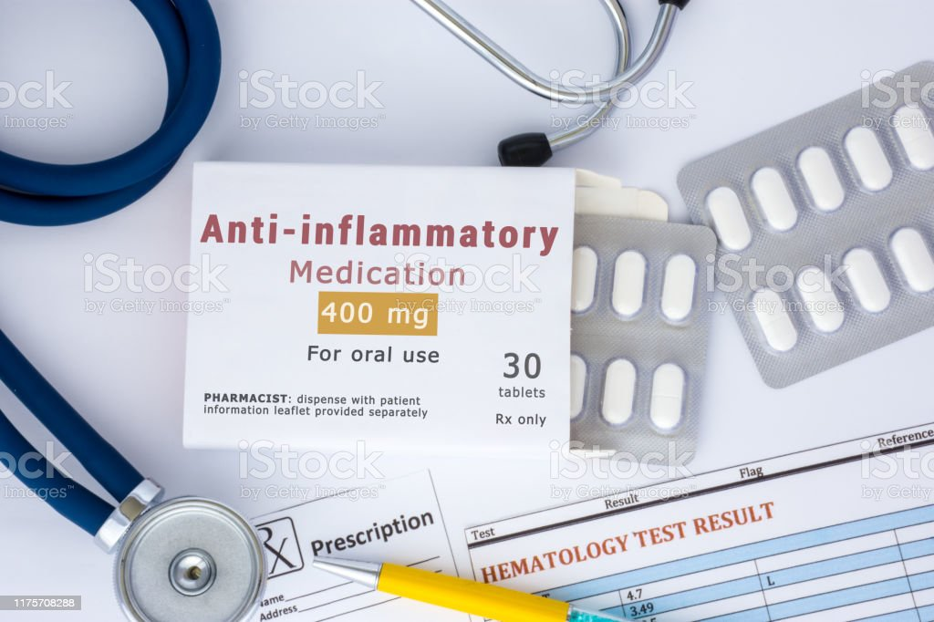 "Anti-inflammatory medication or drug concept photo. On doctor table lies open packaging labeled ""Anti-inflammatory"" and fell out of her blisters with pills for treatment Anti-inflammatory medication or drug concept photo. On doctor table lies open packaging labeled ""Anti-inflammatory"" and fell out of her blisters with pills for treatment Acetaminophen Stock Photo"