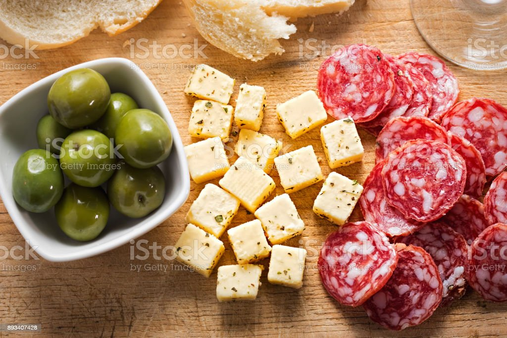 Antipasti - Nocellara del Belice green olives with soft cheese and pepperoni stock photo