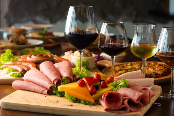 Travessa de antipasti com diferentes produtos de carne e queijo na placa de madeira - foto de acervo