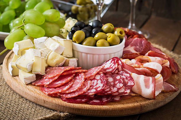 Antipasto catering platter with bacon, jerky, salami, cheese and grapes stock photo
