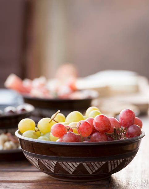 Antipasto Food Classic antipasto food typical of the Mediterranean including grapes, olives, salami in shallow focus shallow stock pictures, royalty-free photos & images