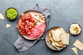 istock Antipasto. Meat platter, chips and sauces, red wine on gray background. Top view 1081735752