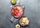 istock Antipasto. Meat platter, chips and sauces, red wine on gray background. Top view 1081735764