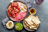 istock Antipasto. Meat platter, chips and sauces, red wine on gray background. Top view 1081735798