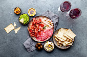 istock Antipasto. Meat platter, chips and sauces, red wine on gray background. Top view 1081735822