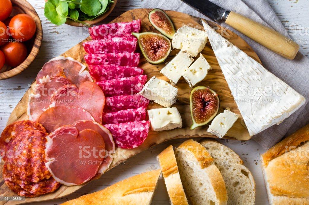 Placa de madeira de antepasto de azeitona com salame, presunto serrano, queijo, nozes e pão ciabatta - foto de acervo