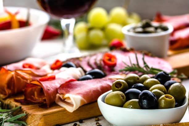 antipasti-platte. wurst, oliven und andere tapas auf tisch, auswahl an speisen aus spanien, mittelmeer-diät - tapas stock-fotos und bilder