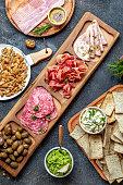 istock Antipasto Platter. Ham serrano, salami olive jamon dip sauces and red wine 1081735330