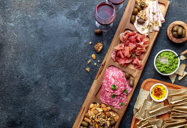 antipasti-platte. serrano schinken, salami oliven jamon dip saucen und rotwein - brotschneidebrett stock-fotos und bilder