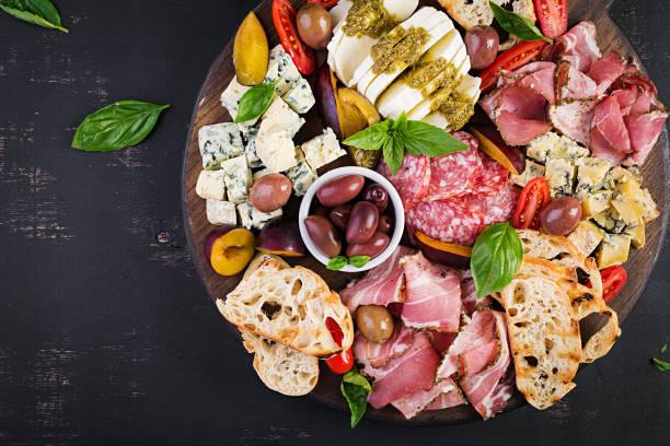 Antipasto-Platte mit Schinken, Schinken, Salami, Blaukäse, Mozzarella mit Pesto und Oliven auf Holzhintergrund. Top-Ansicht, Overhead – Foto