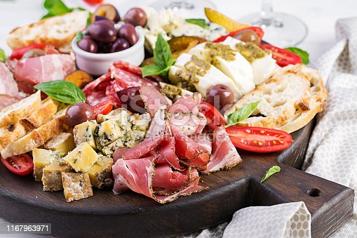 istock Antipasto platter with ham, prosciutto, salami, blue cheese, mozzarella with pesto and olives on a wooden background. 1167963971
