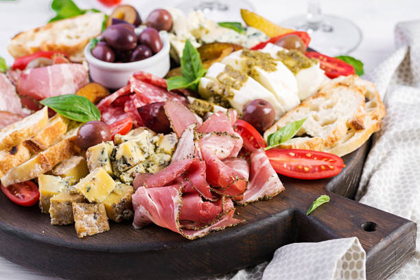 Antipasto platter with ham, prosciutto, salami, blue cheese, mozzarella with pesto and olives on a wooden background. stock photo