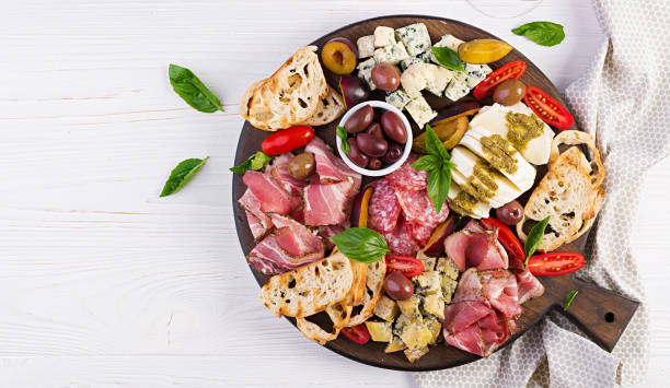 Antipasto platter with ham, prosciutto, salami, blue cheese, mozzarella with pesto and olives on a wooden background. Top view, overhead stock photo
