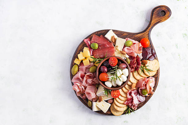 Antipasto platter with ham, prosciutto, salami, cheese,  crackers and olives on a light background.  Christmas table. Top view, overhead stock photo