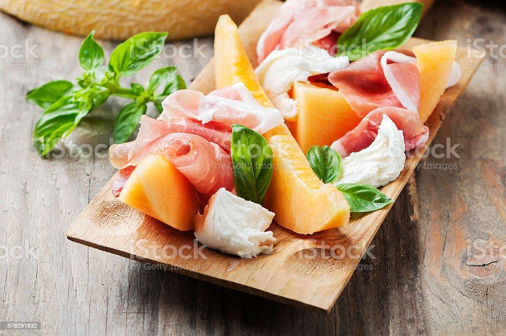 Antipasto with melon, mozzarella, ham and basil stock photo