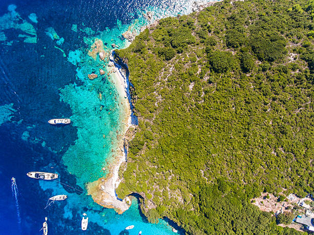 Antipaxos Island, Greece, with sandy beach, people swimming and stock photo