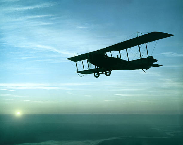 antique airplane flying at sunset, Standard J-1 stock photo
