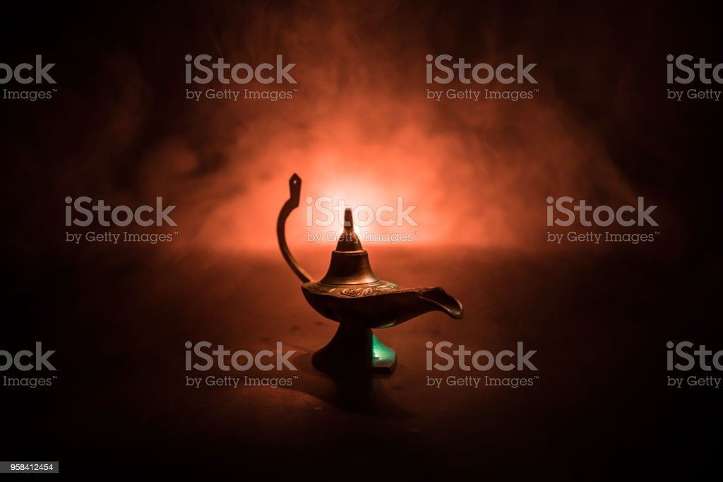 Antique Aladdin arabian nights genie style oil lamp with soft light white smoke, Dark background. Lamp of wishes concept stock photo