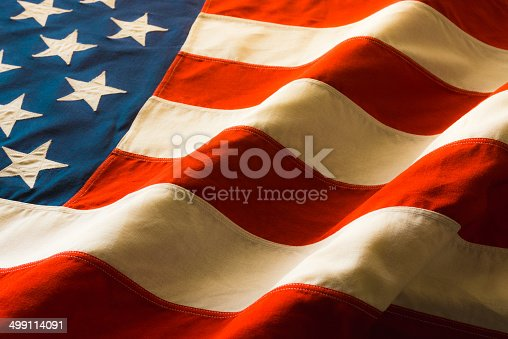 A vintage American Flag lays draped on a table in warm light.