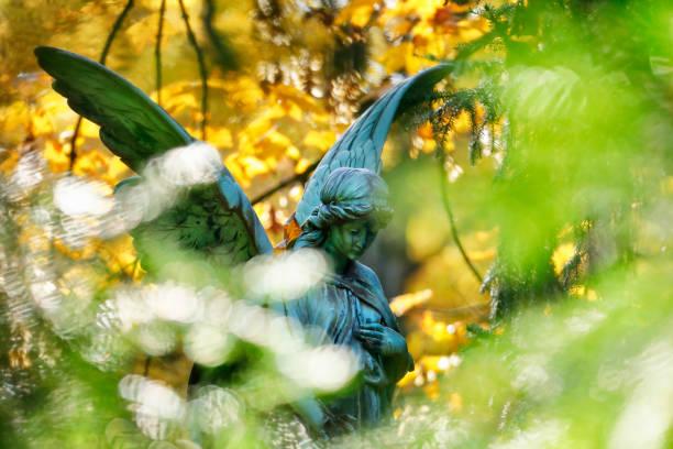 antike engel-statue auf einem friedhof - waldfriedhof stock-fotos und bilder