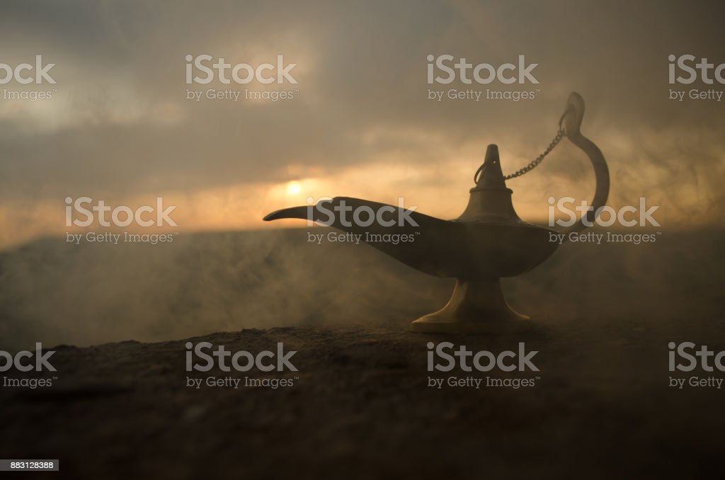 Antique artisanal Aladdin Arabian nights genie style oil lamp with soft light white smoke. Sunset mountain background stock photo