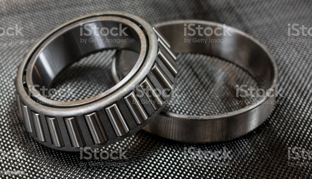 Antique automotive tapered roller bearing and race on plain weave carbon fiber cloth. stock photo
