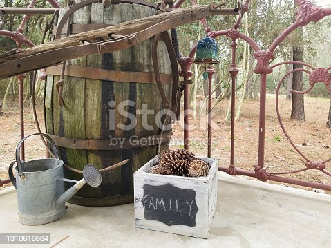 Antique wooden barrel with metal stays.  Hanging from the barrel are parts and pieces of various farm equipment, traps, and tools.